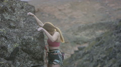 Girl gets to the top of rock climbing route Stock Footage