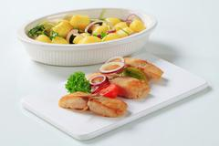 Fish skewer and potatoes in casserole dish Stock Photos