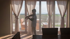 Sun shining on boy in living room play violin 4K Stock Footage