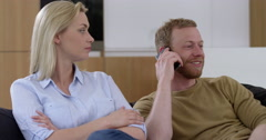 Handsome man chats on cell phone, annoying his girlfriend in contemporary home, Stock Footage