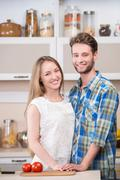 Portrait of a happy smiling couple at kitchen - stock photo