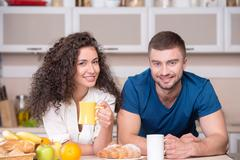 Smiling happy couple drinking morning coffee in the kitchen - stock photo