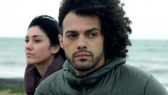 Closeup of handsome angry man with girlfriend in background looking him Stock Footage