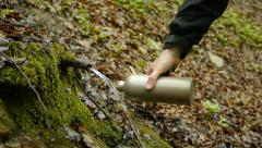Hiker fills canteen with fresh spring water Stock Footage