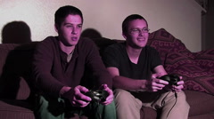 2 guys playing video games. Lit by TV screen. - stock footage