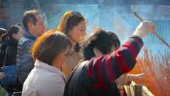 HONG KONG, CHINA - CIRCA JAN 2015: Buddhist worshippers leaving smoldering in Stock Footage