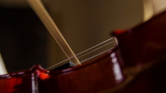 Bow and violin strings playing macro close up 4K - stock footage