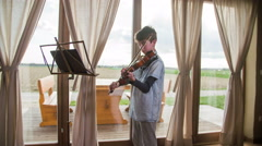 Young violinist playing in front of windows with terrace outside 4K Stock Footage