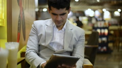 Locked-on shot of a businessman sitting in a cafe and using a digital tablet Stock Footage