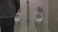 Man using a public bathroom Stock Footage