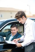 Car dealer and young man signing a contract - stock photo