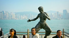 Tourists posing for photos and selfies in front of a bronze statue of Bruce Lee Stock Footage