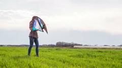 Girl holding wind kite outside on lawn 4K Stock Footage