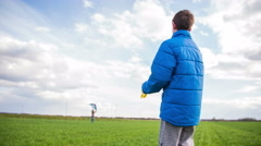 Kid run backwards after wind kite fly in air 4K Stock Footage
