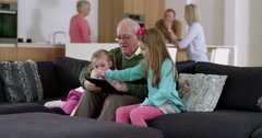 Grandfather plays game on electronic tablet with grand daughters in beautiful Stock Footage