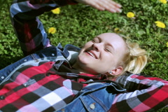 Girl lying on the meadow and covering face because of bright sun Stock Footage