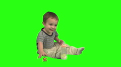 1.5 year old sitting, then putting pacifier in his mouth. Green background. - stock footage