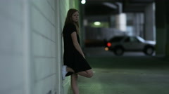 Girl in alley way stares down camera Stock Footage