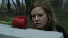 slow motion somber girl visiting grave stone in cemetery - stock footage