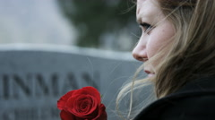 Slow motion somber girl with rose visits gravestone in cemetery Stock Footage