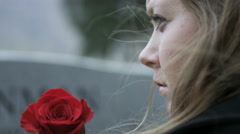 slow motion somber girl with rose visits gravestone in cemetery - stock footage