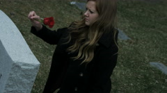 Girl leaves rose on grave stone in cemetery Stock Footage