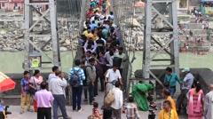 Indian people crossing Laxman Jhula footbridge on river Ganges. Rishikesh, India Stock Footage