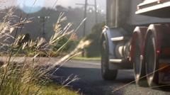 Blured gravel truck brake lights through grass Stock Footage