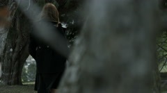 Panning shot woman placing rose in grave stone in cemetery Stock Footage