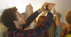 4K Young couple at live music event pose to take a selfie with camera phone - stock footage