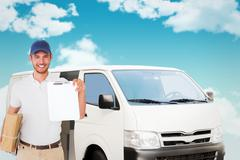 Composite image of happy delivery man holding cardboard box and clipboard - stock photo