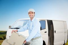 Composite image of confident delivery man pushing trolley of cardboard boxes - stock photo