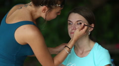Maker up  draws eye shadows to girl Stock Footage
