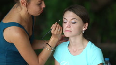 maker up  draws eye shadows to girl - stock footage