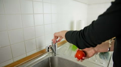 Cleaning tomato under running water jib shot Stock Footage