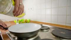 Person add oil to frying pan on electric stove crane shot Stock Footage