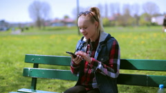 Stock Video Footage of Happy woman sitting on the bench and talking on loudspeaker