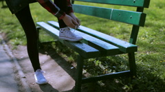 Girl tying shoe laces in the park - stock footage