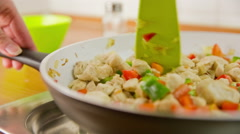 Mixing vegetables and chicken pieces in frying pan close up Stock Footage