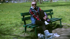 Stock Video Footage of Girl sitting on the bench and changing shoes into rollerblades