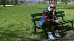 Girl talking on cellphone in the park and wearing rollerblades - stock footage