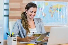 Pretty travel agent reading magazine - stock photo