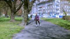 Stock Video Footage of Girl riding on rollerblades in the park and smiling to the camera
