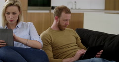 Attractive couple surf on tablets whist ignoring each other, showing what is Stock Footage