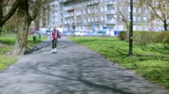 Stock Video Footage of Girl riding on rollerblades and picking up cellphone