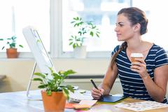 Smiling casual businesswoman working on digitizer and holding coffee - stock photo