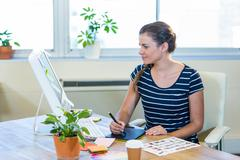 Smiling casual businesswoman working on digitizer Stock Photos