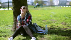 Girl sitting in the park and using bubble blower Stock Footage