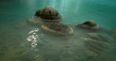 Zen-like nature background of stones in clean blue water of natural pond - stock footage