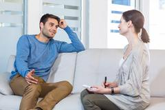 Psychologist talking with happy man Stock Photos